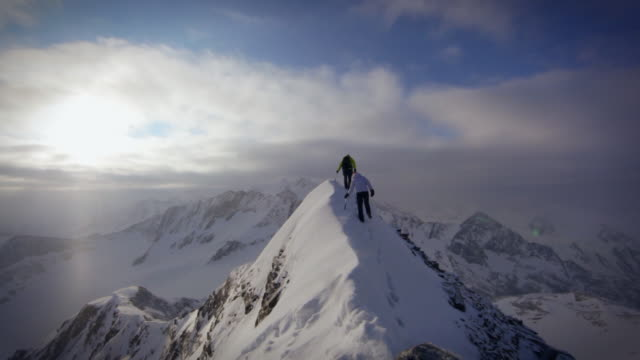 couple of mountain trekkers approaching the summit of a snow covered mountain in the austrian alps.  - newoutdoors stock videos & royalty-free footage