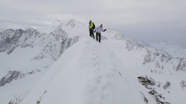 WS TU PAN Couple of mountain trekkers dancing on snow covered mountain in Austrian Alps / Stubai Glacier, Tirol, Austria