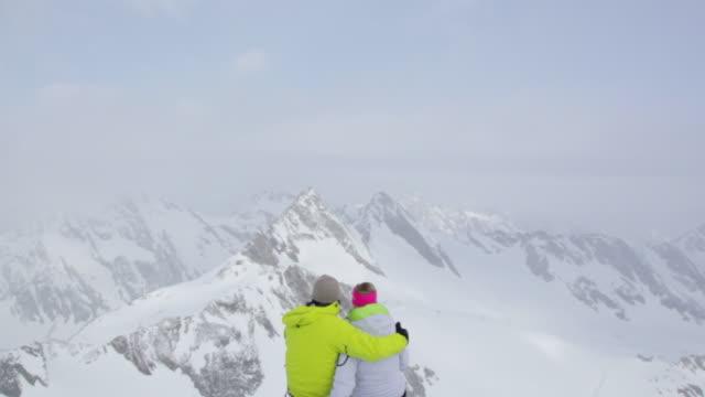 ws td couple of mountain trekkers sitting on snow covered mountain in austrian / stubai glacier, tirol, austria   - 峰点の映像素材/bロール