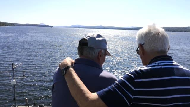 couple of senior men enjoying a sunny summer day by lake memphremagog - gay couple stock videos & royalty-free footage