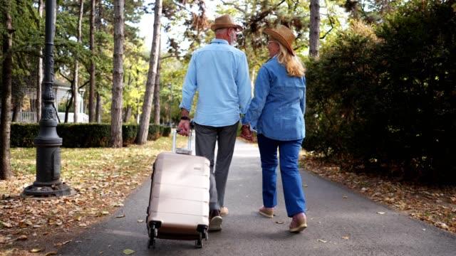 vidéos et rushes de couple de hauts voyageurs profiter de leur temps dans un parc public - valise