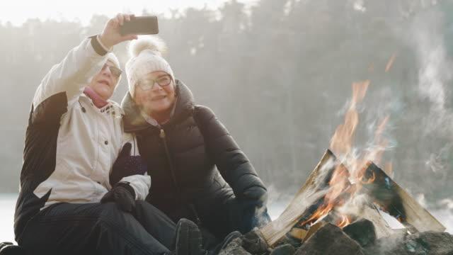 par äldre kvinnor tar selfies vid lägerelden - vedbrasa bildbanksvideor och videomaterial från bakom kulisserna