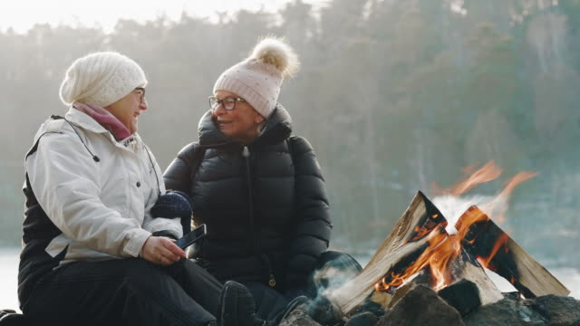 couple of senior women are taking selfies by the campfire - activity stock videos & royalty-free footage
