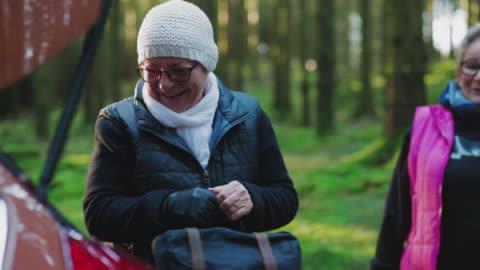 stockvideo's en b-roll-footage met een paar senior vrouwen wandelen door een bos - rugzak