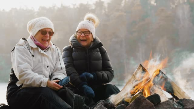 a couple of senior women sitting in front of campfire cinemagraph - cinemagraph stock videos & royalty-free footage