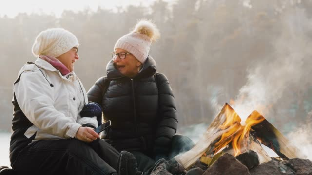 a couple of senior women sitting in front of campfire cinemagraph - active lifestyle stock videos & royalty-free footage