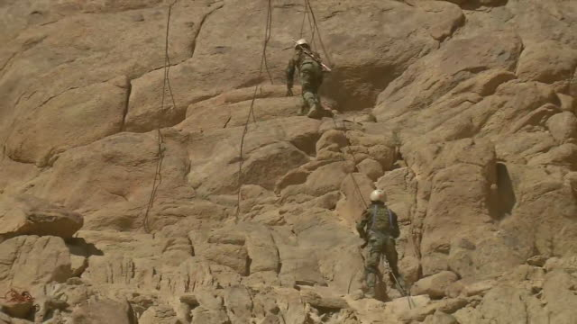 a couple of soldiers from the indian army getting themselves more prepared for the hills one of them can be seen climbing the hill while the other... - indian army stock videos & royalty-free footage