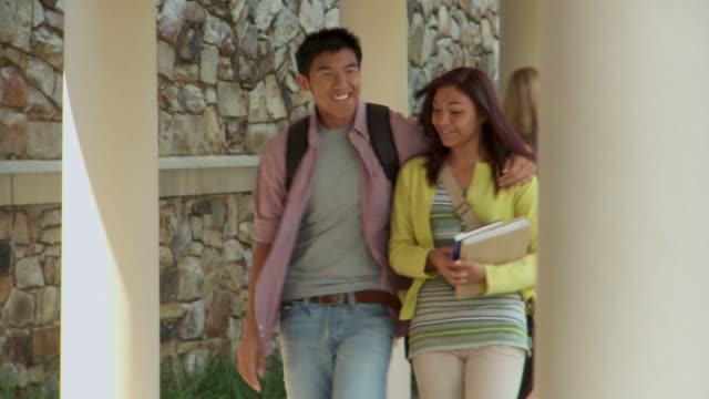 ms, couple of students (14-19) walking along school walkway; richmond, virginia, usa - popolazione dell'asia orientale video stock e b–roll