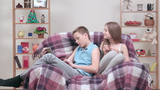 Couple of teenagers enjoying free-time together, sitting in cosy armchair