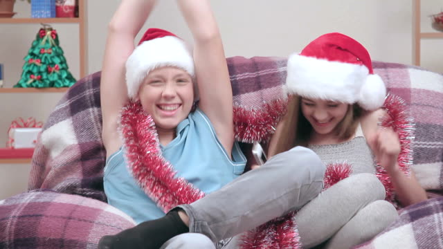 couple of teenagers in santa claus hats, talking on speakerphone. - teenage couple stock videos & royalty-free footage