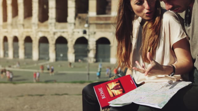 couple of tourists in rome by the coliseum with a tourist guide - gruppo organizzato video stock e b–roll