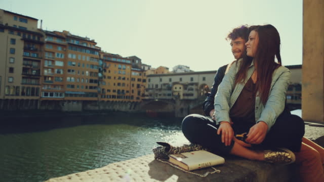 couple of tourists near ponte vecchio, florence - florence italy stock videos & royalty-free footage