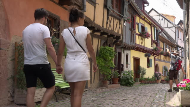 a couple of tourists walk in a alley with half-timbered house - france stock videos and b-roll footage