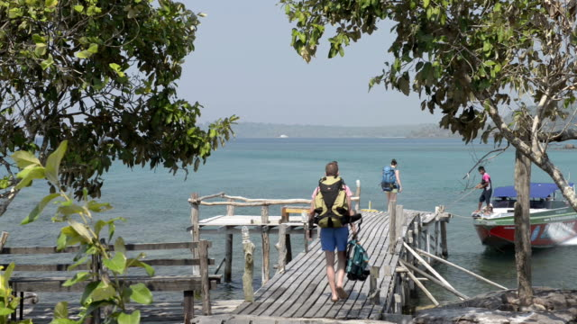 a couple of tourists walk on wooden jetty to speedboat - gulf of thailand stock videos & royalty-free footage