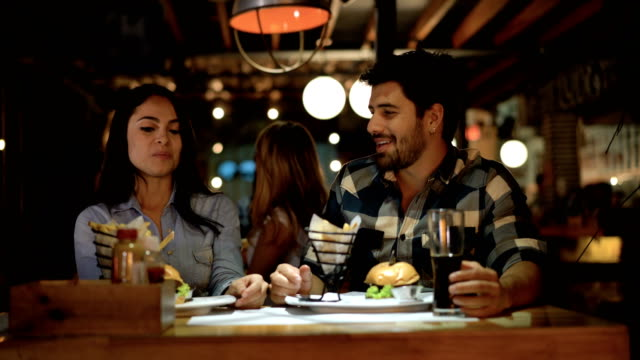 Couple on a date and woman giving a taste of her food to her partner