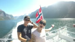 Couple on a fjord boat tour with a Norwegian flag waving behind them, Songefjorden Norway. The motor of the ship makes the water wavy and foamy. Lush green mountains surrounding the fjord. Strong wind
