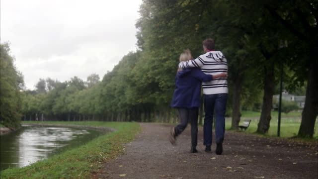 couple on a footpath by a canal, sweden. - cinquantenne video stock e b–roll