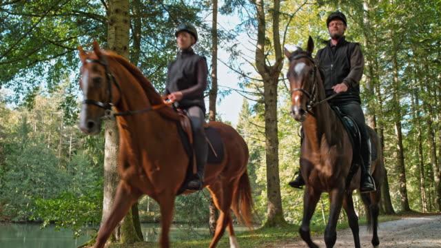 slo mo ds couple on a horseback ride along a lake - bridle stock videos & royalty-free footage