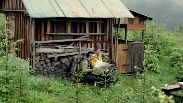 couple on a road trip. picking direction with a map. log cabin - log cabin stock videos & royalty-free footage