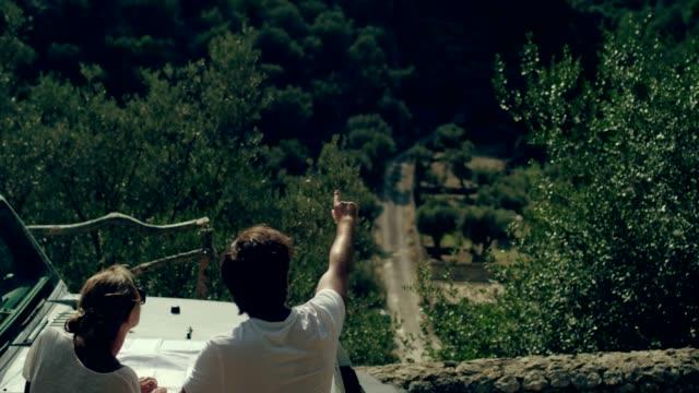 vídeos de stock e filmes b-roll de couple on a road trip. picking direction with a map - carro 4x4