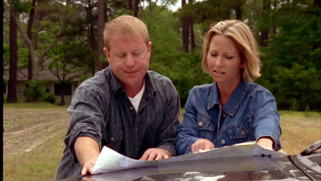 a couple on a road trip studies a map on the hood of their car. - road map stock videos & royalty-free footage