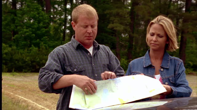 a couple on a road trip unfolds a map on the hood of their car. - road map stock videos & royalty-free footage