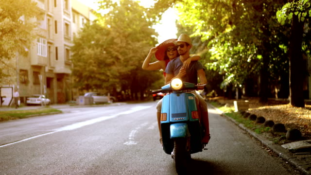 couple on a scooter bike driving through city streets. - motorino video stock e b–roll