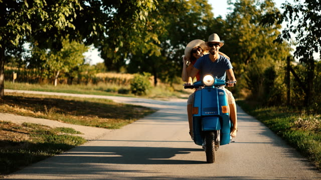 Couple sur un vélo scooter volant à travers la campagne.