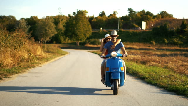 couple on a scooter bike driving through countryside. - motorino video stock e b–roll