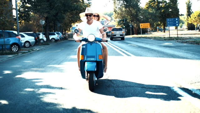 couple on a scooter riding through a city. - motorino video stock e b–roll