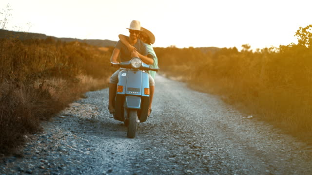 Couple on a scooter riding through a countryside.