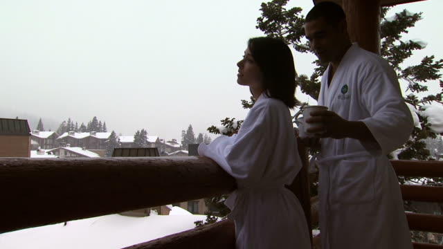 a couple on a snowy balcony drinking coffee - see other clips from this shoot 1169 stock videos & royalty-free footage