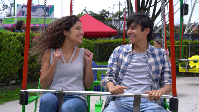 vidéos et rushes de couple sur une balançoire rouler en attendant de commencer à regarder très heureux tout en parlant - monter sur un moyen de transport