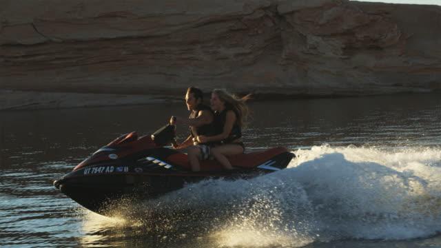 vídeos de stock e filmes b-roll de couple on a wave runner - lago powell