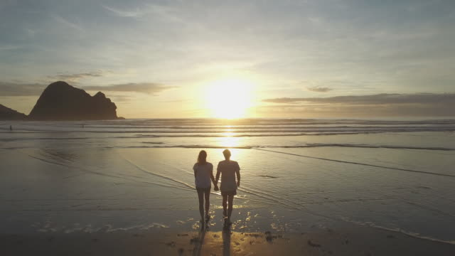 couple on beach at sunset - romantic sky stock videos & royalty-free footage
