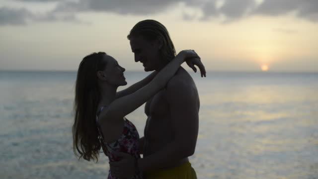 vídeos y material grabado en eventos de stock de couple on beach at sunset - traje de baño de una pieza