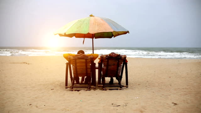 vídeos de stock, filmes e b-roll de casal na praia, goa - chapéu de sol