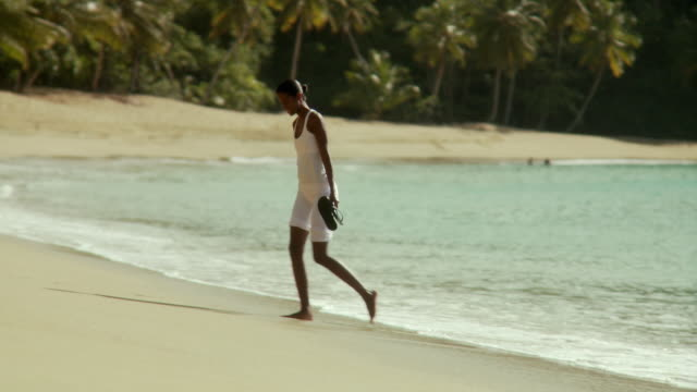 ws pan couple on beach, woman cleaning her slippers on beach / scarborough, tobago, trinidad and tobago   - trinidad trinidad and tobago stock videos & royalty-free footage