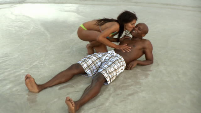 ms couple on beach, woman kissing man / south beach, florida, usa - swimwear stock videos & royalty-free footage