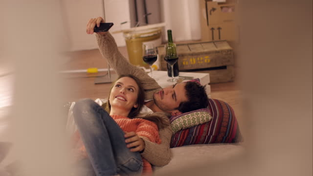 Couple on carpet taking selfies in new apartment