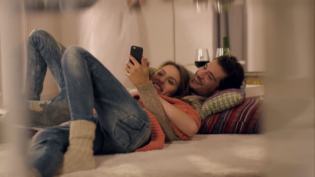 Couple on carpet watching photos on smartphone