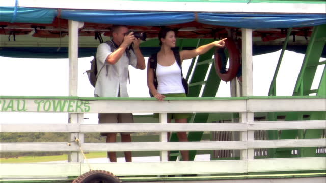 couple on ferry boat taking photographs / the amazon, brazil - paar mittleren alters stock-videos und b-roll-filmmaterial