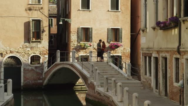 WS Couple on footbridge over canal / Venice