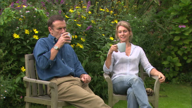 mws couple on garden chairs ifo colourful plants enjoiying - gardening glove stock videos & royalty-free footage