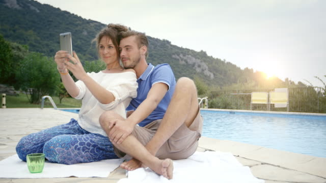 MS ZI Couple on holiday taking photos by the pool outside the town at afternoon / Tourrettes Sur Loup, Provence, France