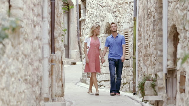 MS Couple on holiday walking through the old town at morning  / Tourrettes Sur Loup, Provence, France