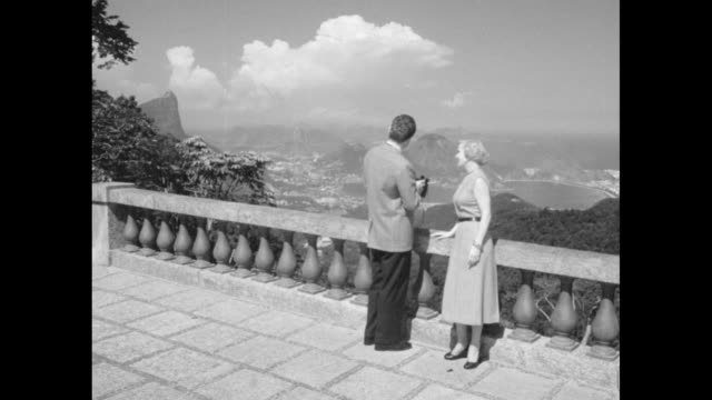 couple on hotel veranda looking at mountains through binoculars as they model fashions / several retakes / note exact day not known - building feature stock videos & royalty-free footage