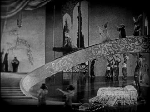 vidéos et rushes de b/w 1924 couple on magic carpet flying out of window of palace / feature - 1924