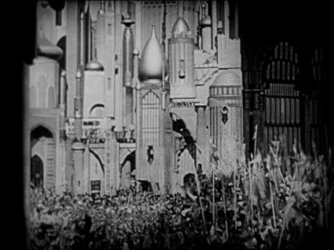 stockvideo's en b-roll-footage met b/w 1924 couple on magic carpet flying over arabian city / feature - 1924