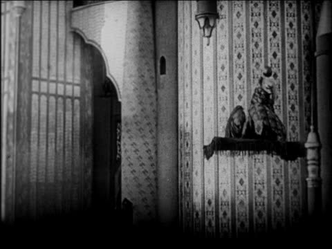 vidéos et rushes de b/w 1924 couple on magic carpet flying thru towers of palace / feature - 1924